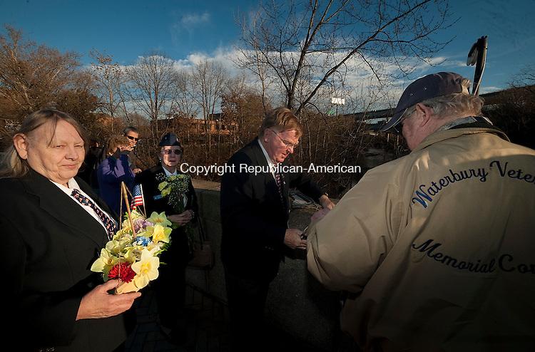 WATERBURY, CT--- -12075JS05--Members of the Waterbury Veterans Memorial Committee, from left, Glora Potter, Bob Dorr and Dan Potter prepare to lower a boat of flowers into the Naugatuck River in Waterbury on Monday during a Pearl Harbor memorial ceremony on the Pearl Harbor Memorial Bridge.   <br /> Jim Shannon Republican-American