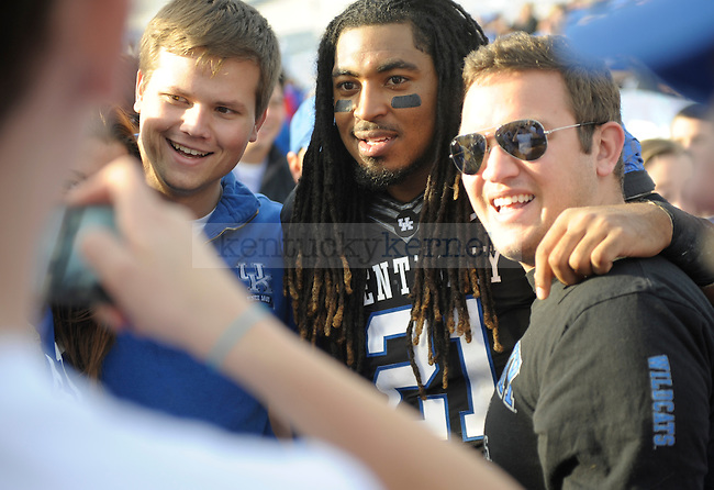 Kentucky Wildcats safety Winston Guy (21) is surrounded and takes pictures with fans after the University of Kentucky football game against Tennessee at Commonwealth Stadium in Lexington, Ky., on 11/26/11. Uk won the game 10-7. Photo by Mike Weaver   Staff