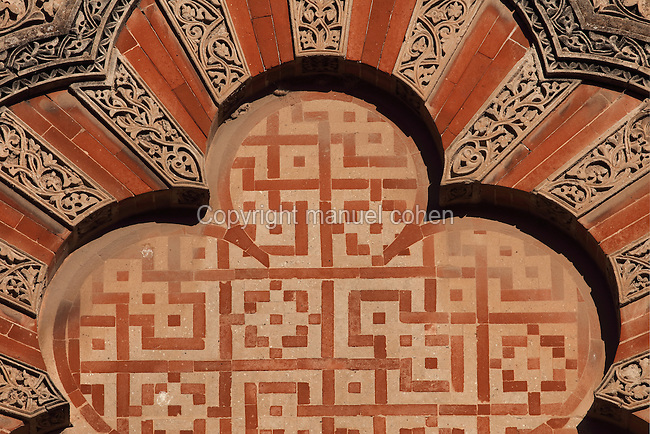 Architectural detail of the Puerta de San Ildefonso, built under Al-Hakam II in the 10th century, one of the West facade entrances to the Cathedral-Great Mosque of Cordoba, on the Calle Torrijos in Cordoba, Andalusia, Southern Spain. This detail shows the intricately carved vegetal patterns, red brick and mosaic work of a fluted arch. The first church built here by the Visigoths in the 7th century was split in half by the Moors, becoming half church, half mosque. In 784, the Great Mosque of Cordoba was begun in its place and developed over 200 years, but in 1236 it was converted into a catholic church, with a Renaissance cathedral nave built in the 16th century. The historic centre of Cordoba is listed as a UNESCO World Heritage Site. Picture by Manuel Cohen