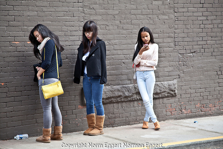 Three teenage girls waiting on a sidewalk