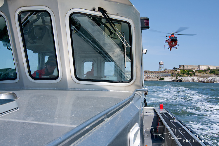 A United States Coast Guard HH-65C Dolphin helicopter approaches a Coast Guard Auxiliary vessel. The helicopter and crew, based at U.S. Coast Guard Air Station San Francisco, was on a practice mission with the Coast Guard Auxilary to maintain search and rescue proficiency.