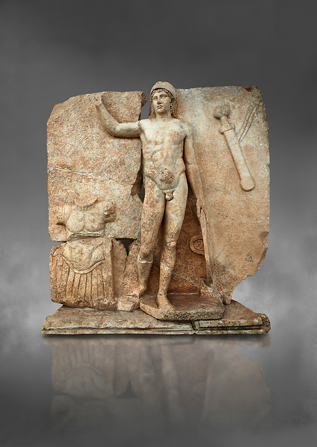 Roman Sebasteion relief  sculpture of Ares, Aphrodisias Museum, Aphrodisias, Turkey.  Against a grey background.<br /> <br /> The nude and classically7 styled young god wears only a helmet and holds a spear (missing) in one hand and a shield in the other. At the left stands cuirass, and at the upper right corner hangs his sword. Ares was a god of war and was not later defaced by Christians probably because he so closely resembles a young emperor.