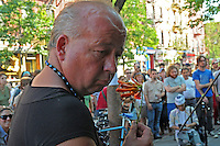 Man with bead necklace and flower at Make Music New York Street Festival in Williamsburg, NYC