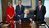 United States President Donald J. Trump looks over the document prior to signing the first of three Executive Order concerning financial services at the Department of the Treasury in Washington, DC on April 21, 2017.  From left to right: US Representative Claudia Tenney (Republican of New York) US Senator David Perdue (Republican of Georgia), the President, and US Secretary of the Treasury Steven Mnuchin.<br /> Credit: Ron Sachs / Pool via CNP