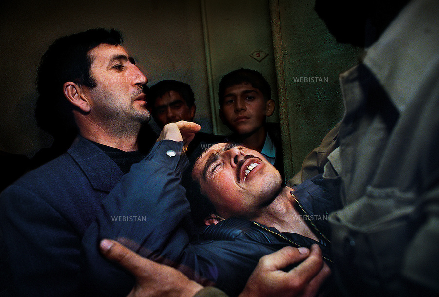 Azerbaijan, Karabakh, Southern Village, February 1992<br /> In a southern village of the Karabakh, a makeshift hospital was set up in a school to tend to all of the wounded Azerbaijanis.A man supports his wounded brother who was shot in the head by an Armenian sniper. Many people were shot directly in the head by professional snipers, many of whom come from other countries to fight in the Karabakh.<br /> <br /> Azerbaidjan, Karabakh, Village du sud, Fevrier 1992 <br /> Dans un village du sud du Karabakh, un hopital de fortune est improvise dans l'ecole pour s'occuper des Azerbaidjanais blesses. Un homme soutient son ami qui vient tout juste de decouvrir le corps de son frere, blesse a la tete par un sniper armenien. Un grand nombre de personnes sont abbatues directement dans la tete par des snipers professionnels, dont beaucoup sont venus d'autres pays pour combattre dans le Karabakh.