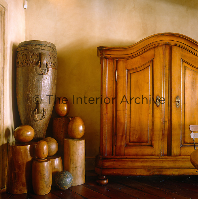 In the dining room an antique cupboard and African artefacts are seen against the subtle pink tones of traditional raw plaster walls