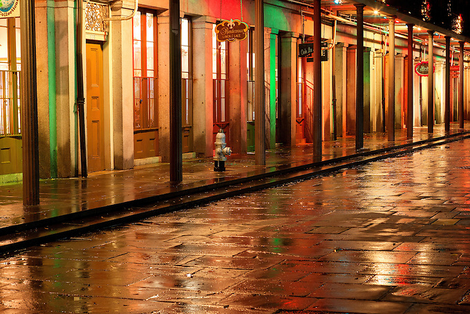 Holiday lights and decorations reflected on the wet streets of Jackson Square at night.