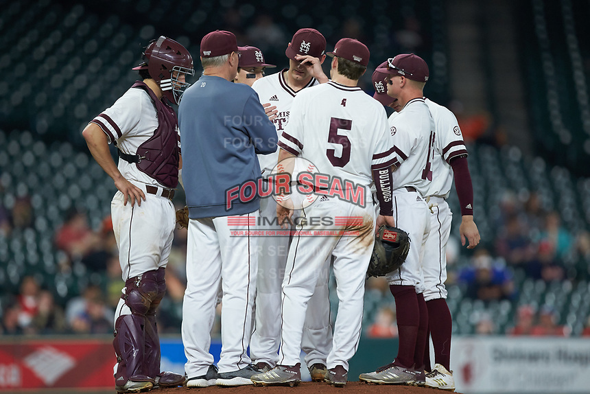 Mississippi State Bulldogs interim head coach Gary Henderson (blue shirt) has a meeting on the mound with starting pitcher Ethan Small (44) and the Bulldogs infield during the game against the Houston Cougars in game six of the 2018 Shriners Hospitals for Children College Classic at Minute Maid Park on March 3, 2018 in Houston, Texas. The Bulldogs defeated the Cougars 3-2 in 12 innings. (Brian Westerholt/Four Seam Images)