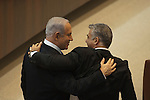Israel's Prime Minister Benjamin Netanyahu, left, and upcoming Minister of Finance Yair Lapid, right, greet each other as they gather for the swearing-in of the new government, at the Knesset in Jerusalem.