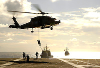 Explosive Ordnance Disposal personnel fast rope onto the deck of USS Abraham Lincoln.