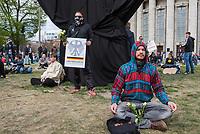 """Auf und rund um den Rosa-Luxemburg-Platz in Berlin-Mitte haben am Samstag den 25. April 2020 mehrere hundert Menschen gegen die Einschraenkungen im Zuge der Massnahmen zur Eindaeemung der Covid-19-Pandemie protestiert. Rechtsextremisten, Hooligans, Antisemiten, Verschwoerungstheoretiker und AfD-Politiker hatten zu einer sogenannten """"Hygiene-Demo"""" versammelt. Vereinzelt protestierten Menschen am Rande gegen diese Demonstration.<br /> Die Polizei war mit mehreren hundert Beamten im Einsatz und nahm mehr als 100 Personen fest.<br /> Im Bild: Ein Demonstrant tut so, als ob er meditiert, wozu die Organisatoren aufgerufen hatten, um ein Verbot der Demonstration zu umgehen.<br /> Im Hintergrung haelt ein Hooligan ein Plakat mit der Aufschrift """"Grundgesetz"""".<br /> 25.4.2020, Berlin<br /> Copyright: Christian-Ditsch.de<br /> [NUR FUER REDAKTIONELLE ZWECKE! Werbung nur auf Anfrage beim Fotografen. Inhaltsveraendernde Manipulation des Fotos nur nach ausdruecklicher Genehmigung des Fotografen. Vereinbarungen ueber Abtretung von Persoenlichkeitsrechten/Model Release der abgebildeten Person/Personen liegen nicht vor. NO MODEL RELEASE! Don't publish without copyright Christian-Ditsch.de, Veroeffentlichung nur mit Fotografennennung, sowie gegen Honorar, MwSt. und Beleg. Konto: I N G - D i B a, IBAN DE58500105175400192269, BIC INGDDEFFXXX, Kontakt: post@christian-ditsch.de<br /> Bei der Bearbeitung der Dateiinformationen darf die Urheberkennzeichnung in den EXIF- und  IPTC-Daten nicht entfernt werden, diese sind in digitalen Medien nach §95c UrhG rechtlich geschuetzt. Der Urhebervermerk wird gemaess §13 UrhG verlangt.]"""
