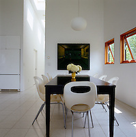In the open plan living/dining area 'Oh' dining chairs by Karim Rashid surround the long dining table designed by Peter Franck and Kathleen Triem