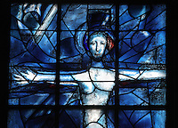 Christ's crucifixion, stained glass window, 1974, by Marc Chagall, 1887-1985, with the studio of Jacques Simon, in the axial chapel of the apse of the Cathedrale Notre-Dame de Reims or Reims Cathedral, Reims, Champagne-Ardenne, France. The cathedral was built 1211-75 in French Gothic style with work continuing into the 14th century, and was listed as a UNESCO World Heritage Site in 1991. Picture by Manuel Cohen