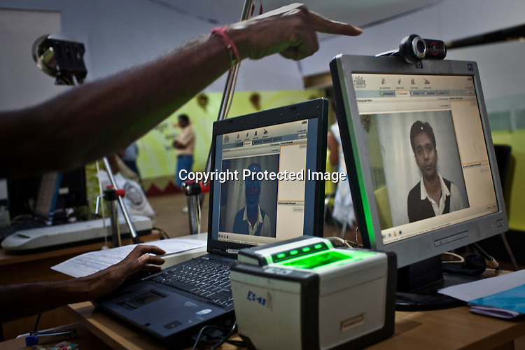 An employee instructs a local resident to look at the camera while he sits in front of camera for the enrollment process in Karnataka, India. For national security reasons and to improve monitoring of citizens, India is issuing each one of its 1.2 billion people with a unique ID card and number based on a photograph, digital finger print and iris scan. Photograph: Sanjit Das/Panos