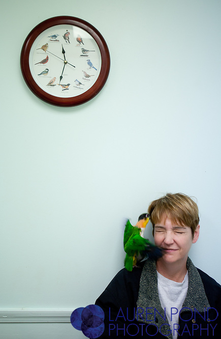 """Harley,"" a black-headed Caique parrot, and ""Sam,"" an orange-headed Caique parrot, both belonging to Jonda Vance, climb and flap on their owner in an exam room at the Avian Health Clinic Inc. in Reynoldsburg, Ohio, on Oct. 27, 2012. Vance lives near Granville, Ohio, and is a member of Columbus Ohio Friends of a Feather, a local bird group in which Mohan is also involved."