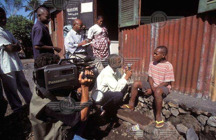 © Giacomo Pirozzi / Panos Pictures..COMOROS..Local television crew interviewing a street kid.