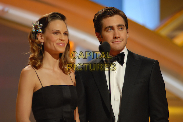 """HILARY SWANK & JAKE GYLLENHAAL.Present the award for Best Screenplay motion picture.Telecast - 64th Annual Golden Globe Awards, Beverly Hills HIlton, Beverly Hills, California, USA..January 15th 2007. .globes half length stage black bow tie dress diamond flower hair accessory.CAP/AW.Please use accompanying story.Supplied by Capital Pictures.© HFPA"""" and """"64th Golden Globe Awards"""""""