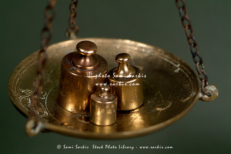 Group of French copper weights hanging on a scale.