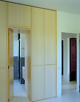 The door to a bathroom forms part of a series of cupboards which line the bedroom walls