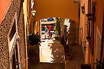 Looking down a narrow path between houses to the water in Varenna, Italy on Lake Como