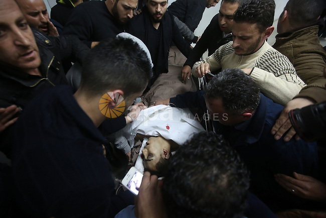 Relatives mourn over the body of Palestinian Shadi Zuhdi Arafah, 28, who was killed by Israeli security forces at the scene of a shooting attack in Gush Etzion settlement, at a hospital morgue in the West Bank city of Hebron, November 19, 2015. Two Israelis and a Palestinian bystander were killed and at least 10 injured in a shooting attack in the Gush Etzion settlement bloc on Thursday, hours after two Israelis were killed in a stabbing attack in Tel Aviv, Israeli police said. Photo by Wisam Hashlamoun