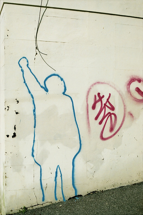 A blue outline on a white exterior wall of a man with raised fist.