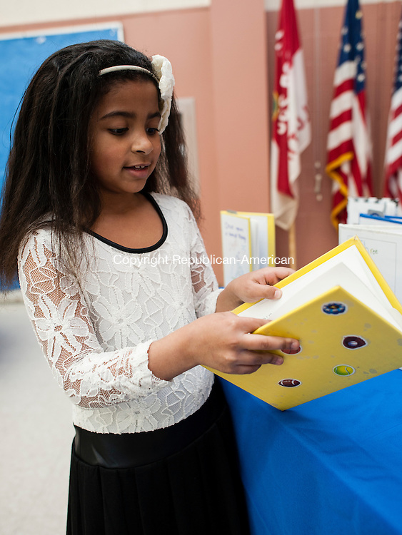 WOLCOTT, CT-9 April 2014-040914EC05-  First grader Lauryn Sinclair looks at her book displayed at Wakelee Elementary School's Young Authors night. The event featured over a dozen elementary school aged authors. The annual program started over 30 years ago by a now retired teacher. Erin Covey Republican-American