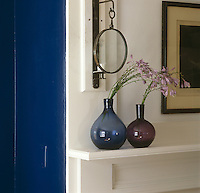 A wrought-iron candle sconce on one side of a simple white-painted mantelpiece in the dark blue dining room