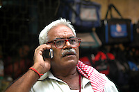 An old Indian man using a mobile phone on a road of  Kolkata, West Bengal,  India   Arindam Mukherjee