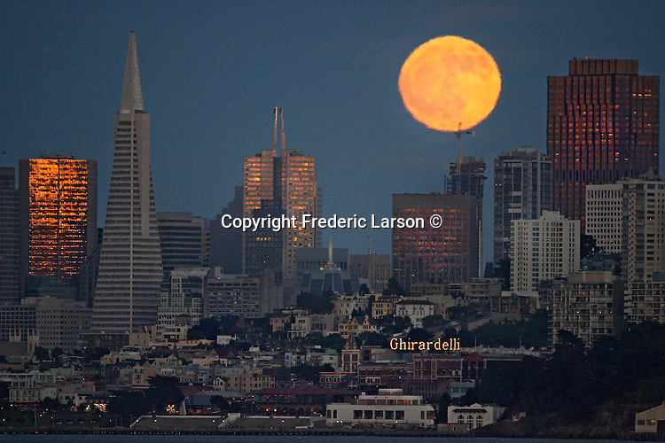 The June full moon decorated San Francisco skyline Friday evening while the sunset reflected golden glow off tall buildings.