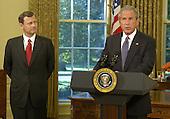 Washington, D.C. - September 5, 2005 -- Federal Judge John G. Roberts, left,  listens as United States President George W. Bush nominates him to succeed Supreme Court Chief Justice William Rehnquist, 5 Septmeber 2005, in the Oval Office. Roberts, who was first nominated to replace retired Justice Sandra Day O'Connor, is to begin confirmation hearings before the Senate Judiciary Committee this week.  .Credit: Mike Theiler - Pool via CNP