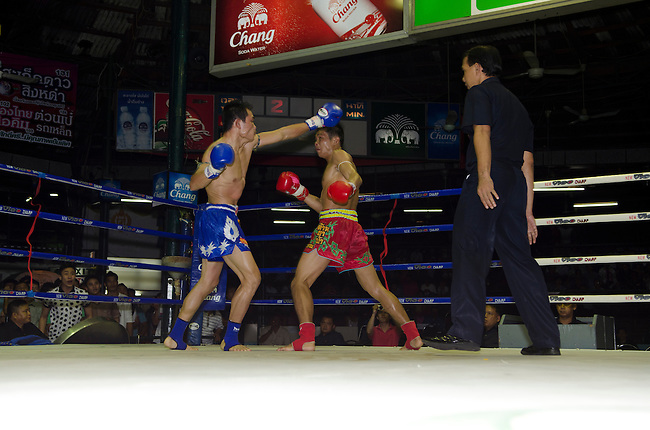 Bangkok, August 30,2011 Lumpini Muay Thai boxing stadium. Yokpetch (blue trunks) swings and misses at Singsiam during their fight.