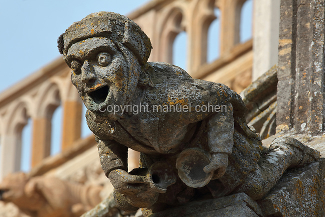 Gargoyle in the form of a man with open mouth holding a jug and bowl, on the facade of the Basilique Notre-Dame de l'Epine, or Basilica of Our Lady of the Thorn, L'Epine, Marne, Champagne-Ardenne, France. The church was built 1405-1527 in Flamboyant Gothic style, is listed as a historic monument and as a UNESCO World Heritage Site as part of the Santiago de Compostela pilgrimage site. Picture by Manuel Cohen