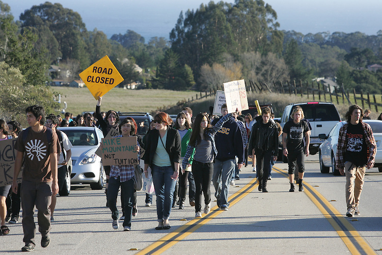 Phil Carter/Sentinel.Protesters march up Empire Grade Road towards the west entrance of UCSC on Wednesday. Hundreds of students set up a blockade at the entrance to the campus.
