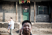 A Chinese man talks on his smartphone in the streets of PingYao, China, July 29, 2014.<br /> <br /> Smartphones are an essential tool of Chinese ordinary life. Everywhere in China, people use them to take pictures to share online, to talk and chat, to play videogames, to get access to the mainstream information, to get connected one each other. In the country where the main global social media are forbidden - Facebook, Twitter and Youtube are not available  -, local social networks such as WeChat have a wide spread all over the citizens. The effect is an ordinary and apparently compulsive way to get easy access to digital technology and modern way of communication. <br /> A life through the display. Yes, We Chat.<br /> <br /> © Giorgio Perottino