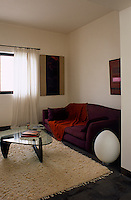 The modern sitting room is furnished with an aubergine sofa and a Noguchi coffee table
