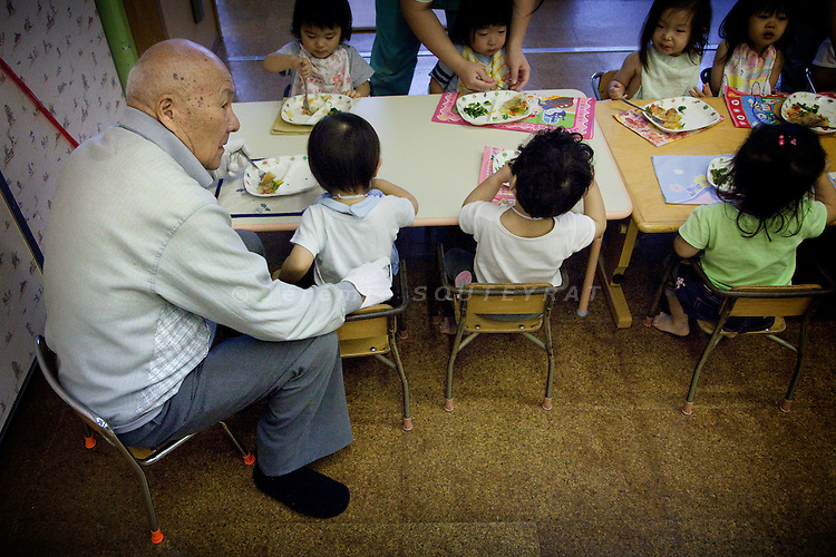 Tokyo - 3rd of December 2009 - Kotohen nursery and nursing home in the Edogawa district. Mr Yamazaki, 71, resident of the nursing home for two years, helps a 2-year-old kid to eat his lunch.