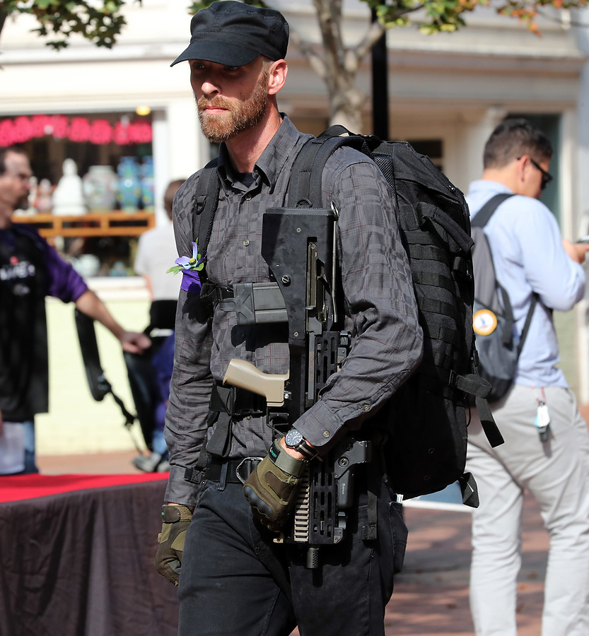 A man patrols the Downtown Mall with a semi-automatic weapon before a memorial for Heather Heyer Wed., August 16, 2017, at the Paramount Theater in Charlottesville, Va. Heyer was killed the previous weekend when a vehicle drove into a crowd of counter-protestors after the Unite The Right rally. Photo/Andrew Shurtleff