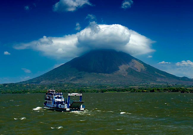 A car ferry heads to Ometepe Island in the rough waters of Lake Nicaragua.  The active Concepcion Volcano looms above.  Ometepe Island is formed by two volcanoes rising from Lake Nicaragua and has been declared a UNESCO Biosphere Preserve.