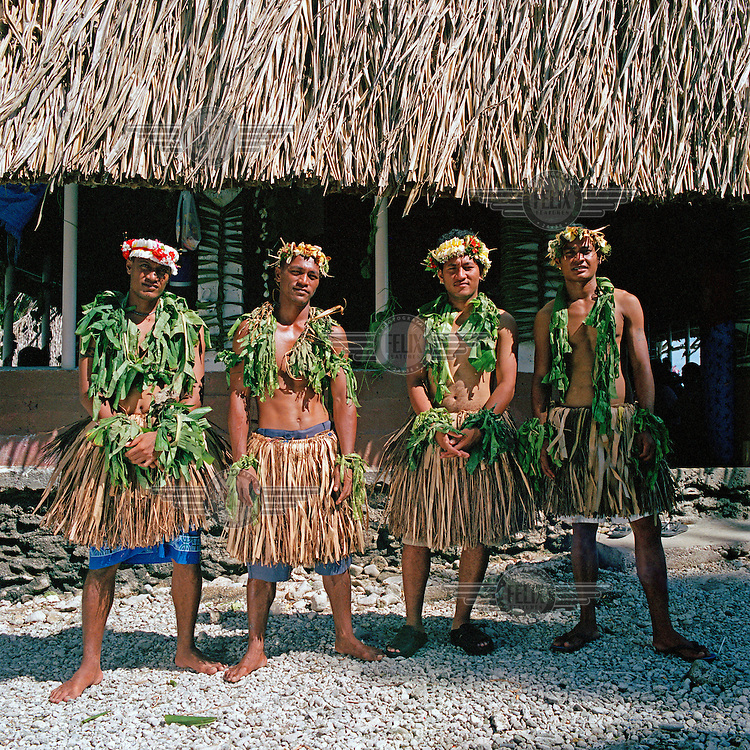 Young Tuvaluan male dancers of the fatele, a traditional local dance, stand in front of the traditional meeting house, or falekaupule.  Dried panadanus leaves are used abundantly across the Pacific in roofing and ceremonial dress.