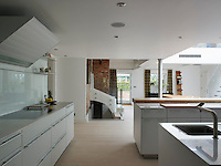 White floorboards and kitchen units create a clean and bright atmosphere in this kitchen dining area
