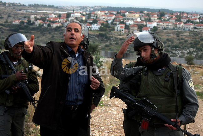 Palestinian man argues with Israeli soldiers during a demonstration against Israel's controversial separation barrier in the West Bank village of Nilin, near Ramallah, on Dec 9, 2009. Israel says the projected 723 kilometres (454 miles) of steel and concrete walls, fences and barbed wire are needed for security. Palestinians view it as a land grab that undermines their promised state. Photo by Issam Rimawi