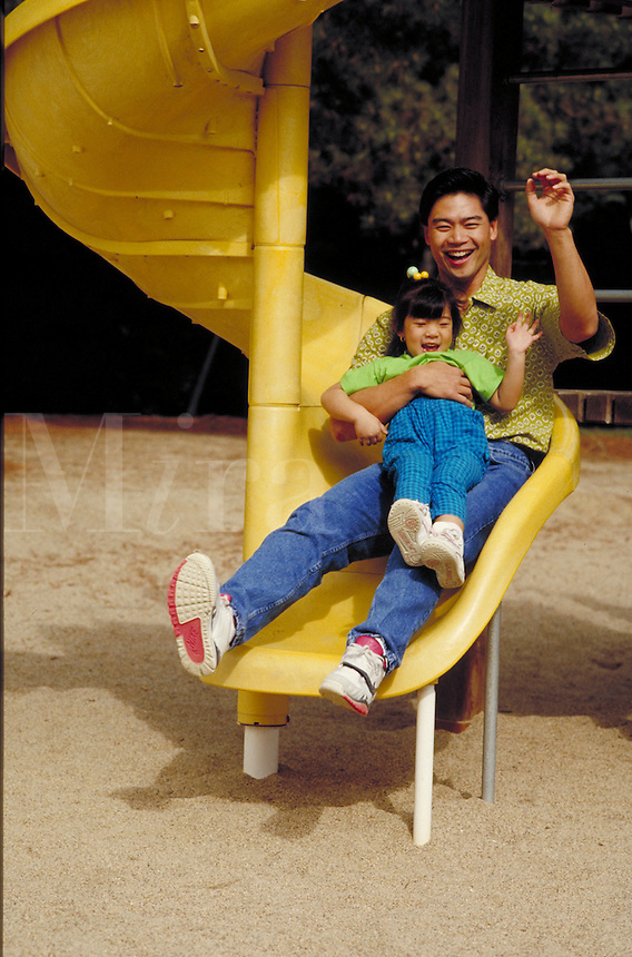 Chinese-American father and daughter playing on a Playscape slide in Roberts Regional Park. Oakland, California.
