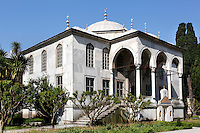 Low angle view of the Enderun Library, or Library of Sultan Ahmed III, 1719, by Mimar Besir Aga, Topkapi Palace, 1459, Istanbul, Turkey. The library has the form of a Greek cross with a domed central hall and three rectangular bays. The fourth arm of the cross consists of the portico (porch), which can be approached by a flight of stairs on either side. Beneath the central arch of the portico is an elaborate drinking fountain (bottom right) with niches on each side. The building is set on a low basement to protect the precious books of the library against moisture. The historical areas of the city were declared a UNESCO World Heritage Site in 1985. Picture by Manuel Cohen.