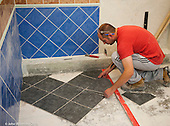 Trainee tiler positioning tiles,  Able Skills training centre, Dartford, Kent.