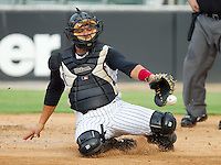 Catcher Miguel Gonzalez #12 of the Kannapolis Intimidators tries to corral the baseball during a South Atlantic League game against the Asheville Tourists at Fieldcrest Cannon Stadium July 26, 2010, in Kannapolis, North Carolina.  Photo by Brian Westerholt / Four Seam Images