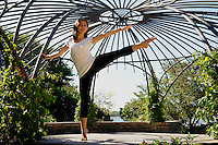 A striking young woman practicing yoga at Toronto Music Gardens