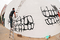 "Dface works on his mural in Bushwick, Brooklyn in New York during the annual Bushwick Collective Block Party on Saturday, June 4, 2016. Music and partying brought some but the real attraction was the new murals  by ""graffiti"" artists that decorate the walls of the buildings that the collective uses.  (© Richard B. Levine)"