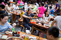 Patrons eat at Ke Wang Shi Chuan Chuan Xiang Huo Guo, a skewer-style hotpot restaurant popular with locals on Tiyu Road in Chongqing, China. Individual servings of meat, vegetables, and tofu, are placed on skewers which diners choose to add to their table's hotpot. The restaurant, which has many favorable online reviews, often has a long wait for tables.