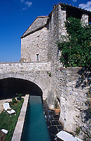 The contemporary swimming pool has been constructed alongside an original stone wall of the chateau beneath a bridge that connects the buildings